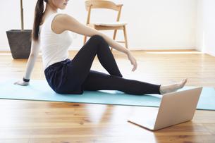 部屋の中で運動をする若い女性の写真素材 [FYI04629011]