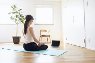 部屋の中で運動をする若い女性の写真素材 [FYI04629017]