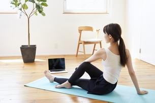 部屋の中で運動をする若い女性の写真素材 [FYI04629020]