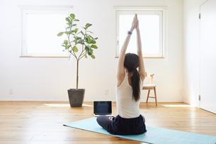 部屋の中で運動をする若い女性の写真素材 [FYI04629022]