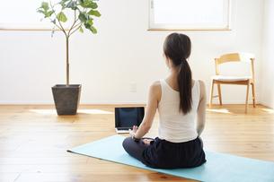 部屋の中で運動をする若い女性の写真素材 [FYI04629025]