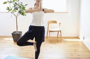 部屋の中で運動をする若い女性の写真素材 [FYI04629030]