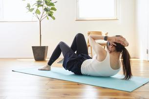 部屋の中で運動をする若い女性の写真素材 [FYI04629033]