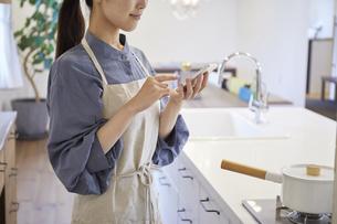 スマートフォンで家電を操作する若い女性の写真素材 [FYI04629055]