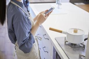 スマートフォンで家電を操作する若い女性の写真素材 [FYI04629056]