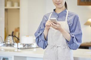 スマートフォンで家電を操作する若い女性の写真素材 [FYI04629057]