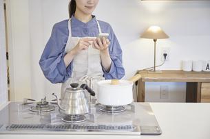 スマートフォンで家電を操作する若い女性の写真素材 [FYI04629066]