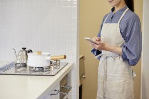 スマートフォンで家電を操作する若い女性の写真素材 [FYI04629067]
