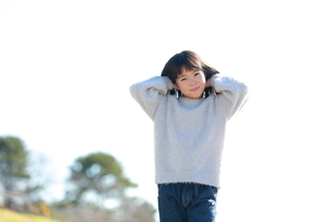 両手を頭の後ろにつける女の子の写真素材 [FYI04629415]