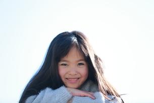 重ねた手に顎を乗せて笑う女の子の写真素材 [FYI04629417]