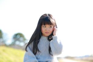 イヤホンをする髪の長い少女の写真素材 [FYI04629418]