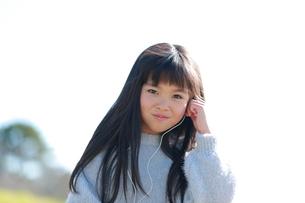 イヤホンをする髪の長い少女の写真素材 [FYI04629419]