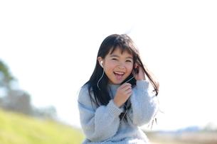イヤホンをする髪の長い笑顔の少女の写真素材 [FYI04629420]
