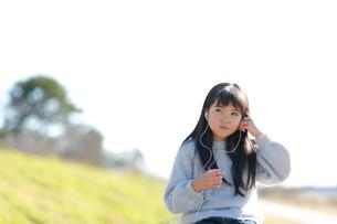 イヤホンをする髪の長い少女の写真素材 [FYI04629422]