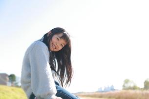座ってこちらを向く笑顔の女の子の写真素材 [FYI04629424]