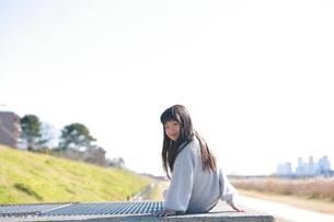 座ってこちらを振り向く髪の長い女の子の写真素材 [FYI04629425]