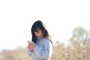 スマートフォンを指で操作する笑顔の少女の写真素材 [FYI04629429]