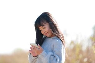 スマートフォンを指で操作する少女の横顔の写真素材 [FYI04629430]