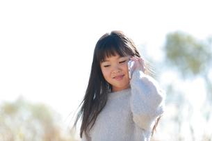 スマートフォンを耳に当てる髪の長い少女の写真素材 [FYI04629432]