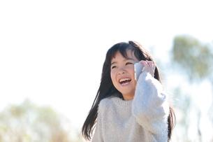 スマートフォンで通話する笑顔の少女の写真素材 [FYI04629433]