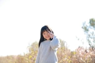 スマートフォンを耳に当てる髪の長い少女の写真素材 [FYI04629434]