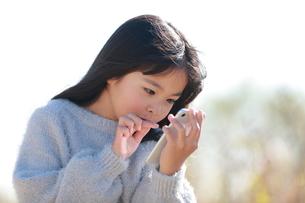 スマートフォンを指で操作する少女の写真素材 [FYI04629435]