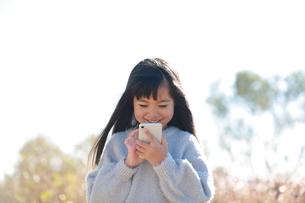 笑顔でスマートフォンを操作する少女の写真素材 [FYI04629436]