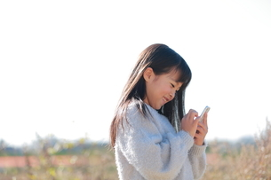 スマートフォンを指で操作する笑顔の少女の写真素材 [FYI04629438]
