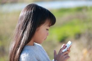 スマートフォンを指で操作する少女の横顔の写真素材 [FYI04629439]
