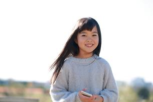 スマートフォンを持ってこちらを見つめる笑顔の少女の写真素材 [FYI04629441]