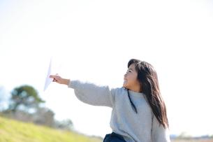 紙飛行機を手に持ち空を見上げる笑顔の少女の横顔の写真素材 [FYI04629443]