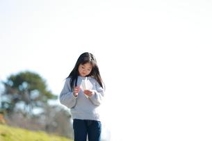 手に紙飛行機を持つ髪の長い少女の写真素材 [FYI04629446]