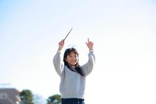 タクトのような棒をふり遊ぶ少女の写真素材 [FYI04629449]