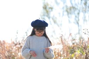 植物を持ちながらうつむく眼鏡をかけた青いベレー帽の少女の写真素材 [FYI04629453]