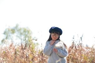 手を顎に当てて植物を見つめる眼鏡をかけた青いベレー帽の少女の写真素材 [FYI04629454]
