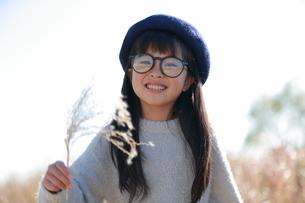 眼鏡と青いベレー帽を身に付けた笑顔の少女の写真素材 [FYI04629455]
