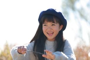 笑顔で木の枝を振り回して遊ぶベレー帽の少女の写真素材 [FYI04629457]