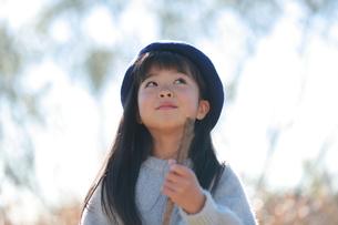 木の枝を持って空を見上げるベレー帽の少女の写真素材 [FYI04629458]