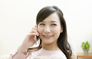 電話をする笑顔の女性の写真素材 [FYI04629730]