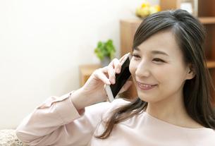 電話をする笑顔の女性の写真素材 [FYI04629731]