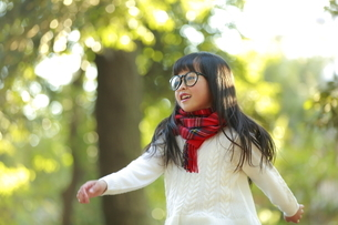 森の中で遊ぶ眼鏡の女の子の写真素材 [FYI04629756]