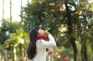 森の中シャボン玉を吹いて遊ぶ女の子の写真素材 [FYI04629767]