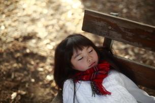 ベンチで眠る女の子の写真素材 [FYI04629768]