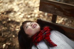ベンチに寝転ぶ女の子の写真素材 [FYI04629769]