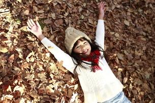 落ち葉に寝転び両手を上げる少女の写真素材 [FYI04629771]
