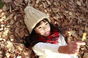 落ち葉に寝そべり葉っぱを見つめる女の子の写真素材 [FYI04629772]
