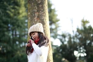 木にもたれて髪をいじるニット帽の女の子の写真素材 [FYI04629777]