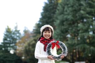 森の中でクリスマスリースを持った笑顔の女の子の写真素材 [FYI04629784]