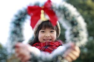 クリスマスリースから覗く帽子をかぶった女の子の写真素材 [FYI04629785]