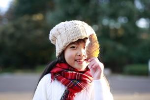 落ち葉を1枚手に持った少女の写真素材 [FYI04629788]